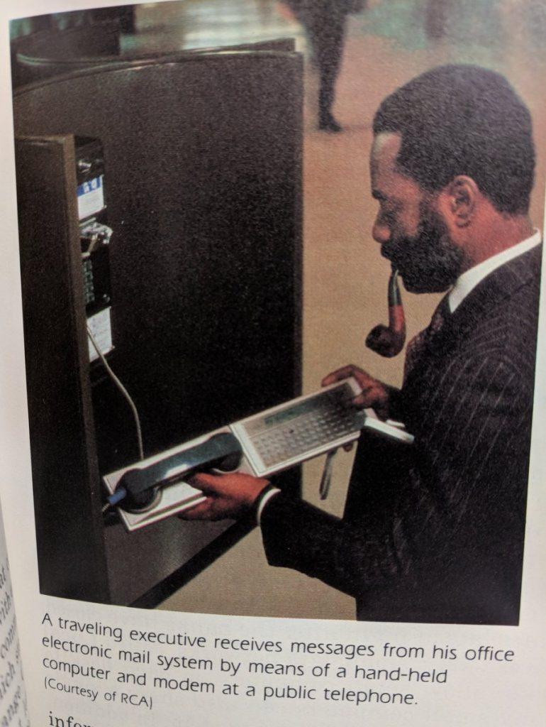 Oude foto van man met baard die een soort modem gebruikt bij een telefooncel
