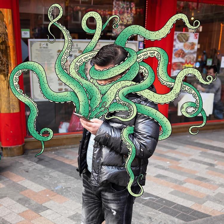 Een octopus komt uit de telefoon van iemand die daar op straat naar staart