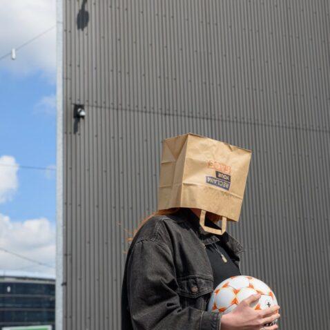 vrouw met papieren zak op hoofd
